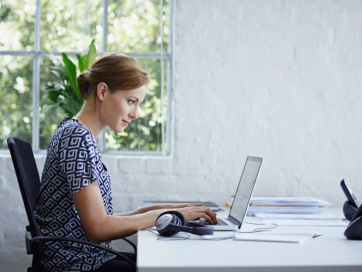 Woman sitting at desk in front of laptop