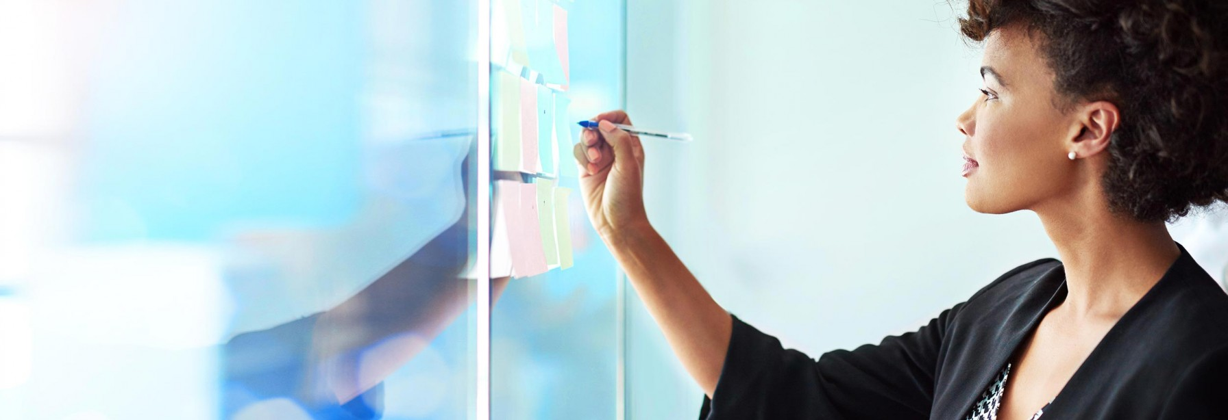 Woman writing on a glass board